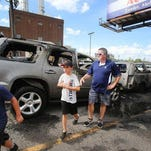 The Noonan family: Cole, 9, left, Parker, 10, center and their dad, Mike, all of Flushing, are reacting to their car being burned in a parking lot at Beaubien and Gratiot in downtown Detroit while they attended a Tigers baseball game Sunday. No one is hurt and the reason for the fire is unknown at this time.