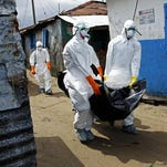 Liberian healthcare workers on an Ebola burial team collect the body of an Ebola victim in Westpoint, Monrovia, Liberia, Saturday.