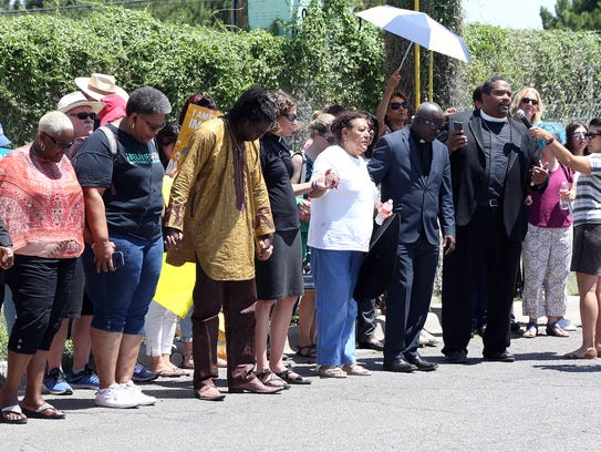 A group of clergy members and others pray Wednesday