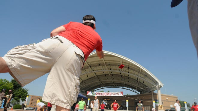 P.J. Jeffers, left, throws a beanbag while teaming up with his brother-in-law, Tony Zahner, far center, during the Midwest Cornhole Championship, a fundraiser for the Boys & Girls Club, at the Leach Amphitheater in Oshkosh Aug. 17, 2013.