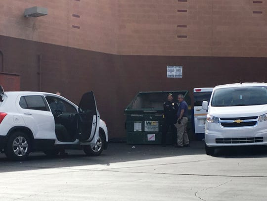 Police at the scene where a body was found in a dumpster