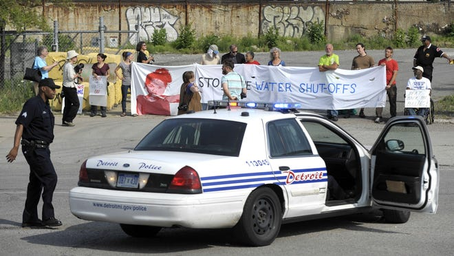 Detroit police officers keep an eye on the protestors who block the entrance to Homrich Inc. in July 2014 in Detroit.