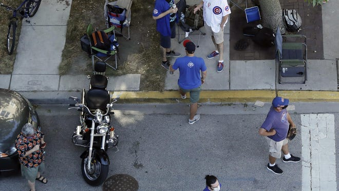 Chicago Cubs fans wait for a ball outside of Wrigley Field before the Opening Day baseball game between the Chicago Cubs and the Milwaukee Brewers in Chicago, Friday, July 24, 2020, in Chicago. In a normal year, that would mean a sellout crowd at Wrigley Field and jammed bars surrounding the famed ballpark. But in a pandemic-shortened season, it figures to be a different atmosphere.