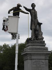 A New Orleans city worker wearing body armor and a face covering measures the Jefferson Davis monument in New Orleans in preparation for its removal.