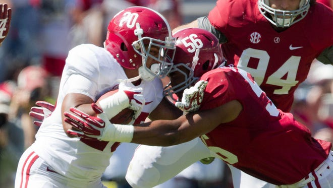 Alabama Crimson Tide running back Tyren Jones (20) is hit by Alabama linebacker Tim Williams (56)  during the A-Day game at Bryant-Denny Stadium.