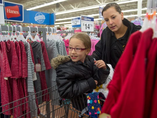Katelynn Brand, 7, looks for clothes with Henderson County Detention Center lieutenant Megan McElfresh during the Fraternal Order of Police Lodge No. 9 Cops and Kids event at Walmart in Henderson, Ky., on Wednesday, Dec. 13, 2017. This year, about 60 children in need shopped with an officer for clothes, toiletries, and other items, with money raised by the Fraternal Order of Police Lodge No. 9. Winter jackets were donated by Columbia Sportswear, and Walmart donated food for the children and their families.