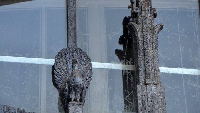 Perched along the large lower windows of Heritage Tower, facing West Michigan Avenue, are a set of 16 figures of some sort of fan-tailed bird.