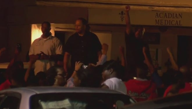 In this image taken from video, residents protest in Baton Rouge, La., following the shooting of a man by police Tuesday.