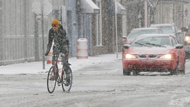 A cyclist carefully navigates wet snow last February at Sixth and Main streets in downtown Lafayette. Snow is in the forecast for Greater Lafayette next weekend.