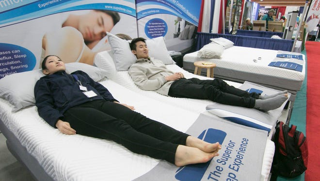 Janice Lee and Albert Liu check out the feel of mattresses at the Superior Sleep Experience booth Sunday, April 15, 2018 at the Livingston County Home Show.