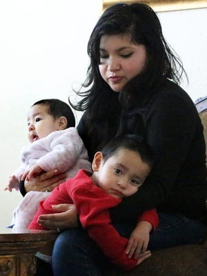 Juaquin Ayers, 2, rests in the arms of his mother, Sandra Ayers, along with his 3-month-old sibling Nova Ayers at their East El Paso home. Juaquin, who suffers from a rare skull condition, will undergo a six-hour surgery in January.