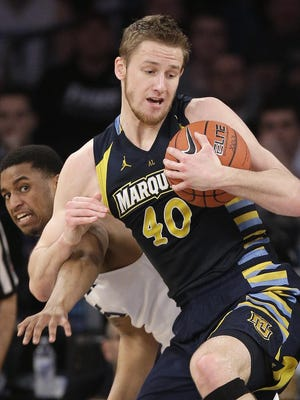 Marquette center Luke Fischer (40) pulls down a rebound against Xavier guard Trevon Bluiett (5) during the first half of an NCAA college basketball game during the Big East men's tournament on Thursday in New York.