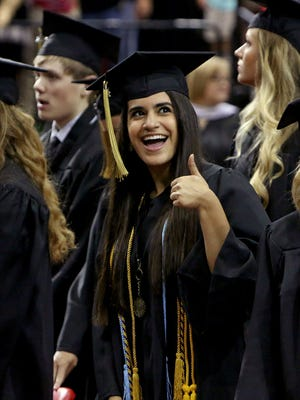 In this 2017 file photo, a Rider High School graduate smiles toward family and friends while walking into the graduation ceremony at Kay Yeager Coliseum.