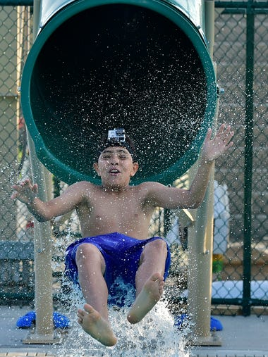 Joshua Ocasio takes the giant green slide to the pool.