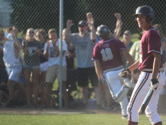 Menomonee Falls junior Henry Hansen is all smiles after Dayne Fuiten scores a run to put the Indians ahead Monday night.