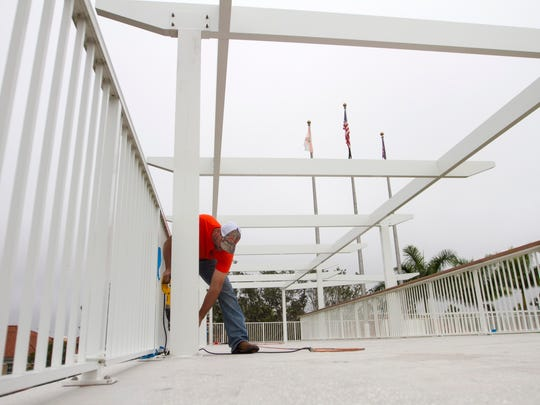 Adam Carley of Architectural Metals works on a canopy at the Century Link Sports Complex on Thursday.