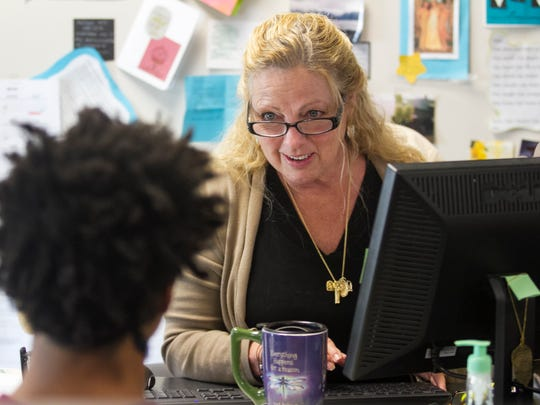 Patty Costello works with a student on Thursday at