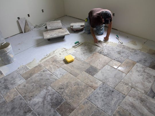 Shawn Jeffries lays tile in a Sinclair Custom Home