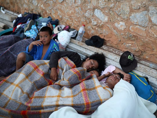 "A boy sits awake as Central American migrants traveling with the annual ""Stations of the Cross"" caravan sleep at a sports club in Matias Romero, Oaxaca State, Mexico, on April 3, 2018."