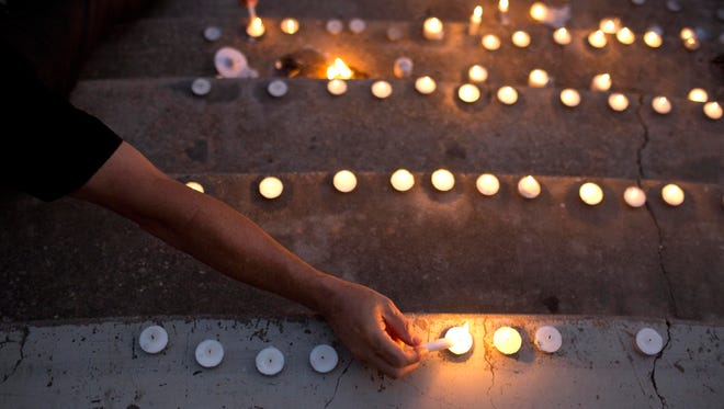 People light candles during a vigil to honor the victims of a deadly shooting in Lafayette, La., on Saturday, July 25, 2015