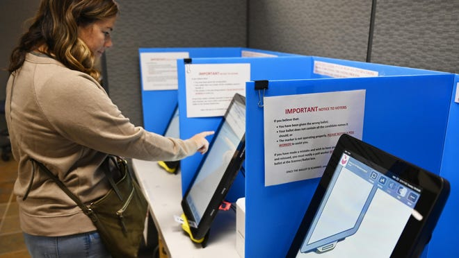 FILE-In this Tuesday, Nov. 5, 2019 file photoCourtney Parker votes on a new voting machine, in Dallas, Ga. Election integrity activists are raising concerns about Georgia's new voting machines, saying the large, bright, vertical touchscreens allow other people in the room to see a voter's selections in violation of ballot secrecy provisions in state law. In a petition filed Monday, Feb. 24, 2020, in Sumter County Superior Court against the five members of the county election board, the activists ask the court to order the board to have voters use hand-marked paper ballots rather than the touchscreen voting machines.