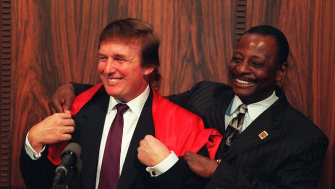 Donald Trump laughs as Mel Farr, right, drapes a cape over Trump's shoulders at a morning press conference at  the Fisher Theater in 1997. The two were partners in a casino venture that never came to fruition.  Farr wore the signature cape in the TV commercials for his auto dealerships.