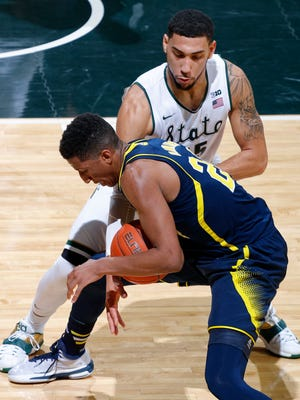 MSU's Denzel Valentine pokes the ball away from Michigan's Aubrey Dawkins for a steal during the first half Sunday in East Lansing. Valentine finished with 25 points, seven rebounds and seven assists as the Spartans won 76-66 in overtime.