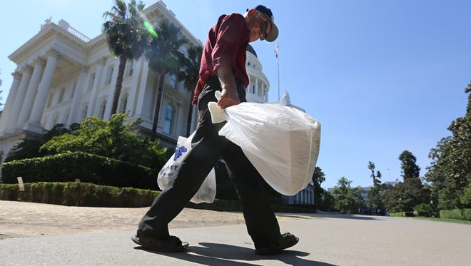 Plastic single-use bags are carried past the State Capitol in Sacramento, Calif., on Aug. 12, 2014.
