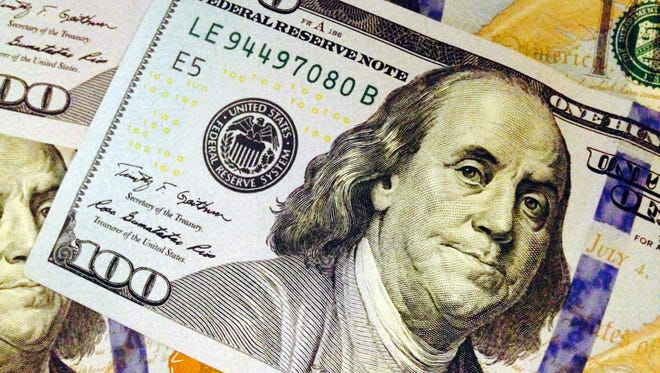 This Feb. 2, 2015, file photo, depicts a part of a U.S. $100 bill. The federal government's two largest benefit programs -- Medicare and Social Security -- face short- and long-term financial problems.