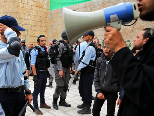 """In this Wednesday, March 22, 2017 photo, a director gives instructions to the actors dressed as Israeli policemen during a shoot of the """"Heaven's Gate"""" movie in a recreated alleyway of Jerusalem's Old City in Khan Younis, Gaza Strip. The set is the latest effort by the al-Aqsa channel, run by Gaza's Islamic militant Hamas rulers, to kick-start its drama production in the territory."""