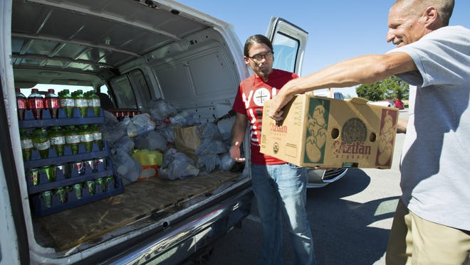 Casa de Peregrinos volunteer Keith Kielpinski, right, hands Michael Barnes a box full of non-perishable food items collected on Saturday, October 15, 2016 by NMSU students for the Feed Las Cruces Food Drive hosted by Casa de Peregrinos.