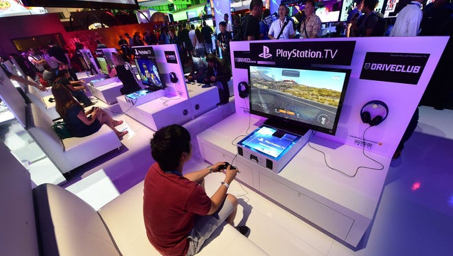 People test the new PlayStation TV consoles at E3 in Los Angeles in 2014.