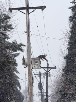 Power lines are repaired by a workman Friday, Nov. 18, in Sartell. Heavy snow and high winds caused several power outages in the area Friday.