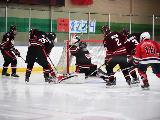 Making one of his 26 saves Wednesday night en route to a shutout is Livonia Churchill goalie Chris Sergison (35).