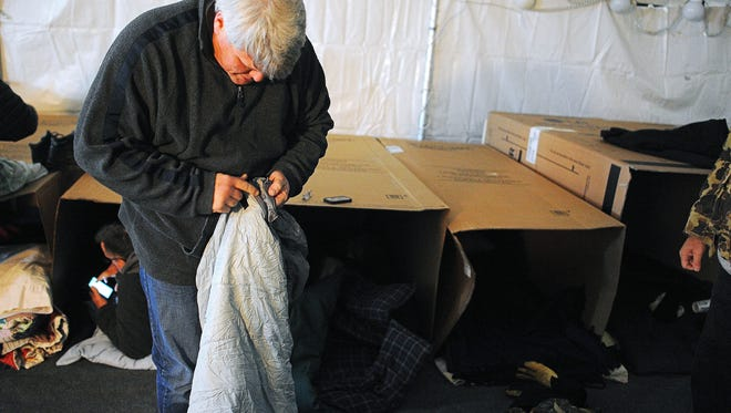 """Argus Leader Media columnist Stu Whitney sets up his cardboard box to sleep in during the Bishop Dudley Hospitality House's sleep out event, """"A Night of Hope for the Homeless"""" in Sioux Falls."""