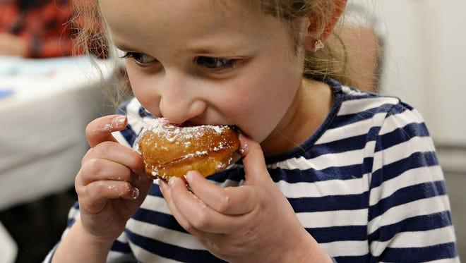 Chaya Gorelik, 7, eats a donut at Chabad of Northern Colorado's Hanukkah party on the second night of Hanukkah, Sunday, December 25, 2016.