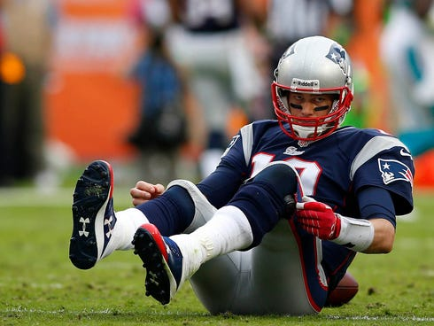 Dec 15, 2013; Miami Gardens, FL, USA:  New England Patriots quarterback Tom Brady (12) on the ground after a sack by Miami Dolphins defensive end Cameron Wake (not pictured) in the second half at Sun Life Stadium. The Dolphins won 24-20. Mandatory Cr