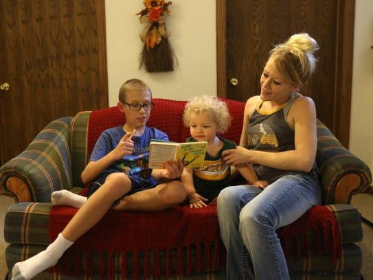 Jordan Tellekson, 11, reads to his little sister Quinn