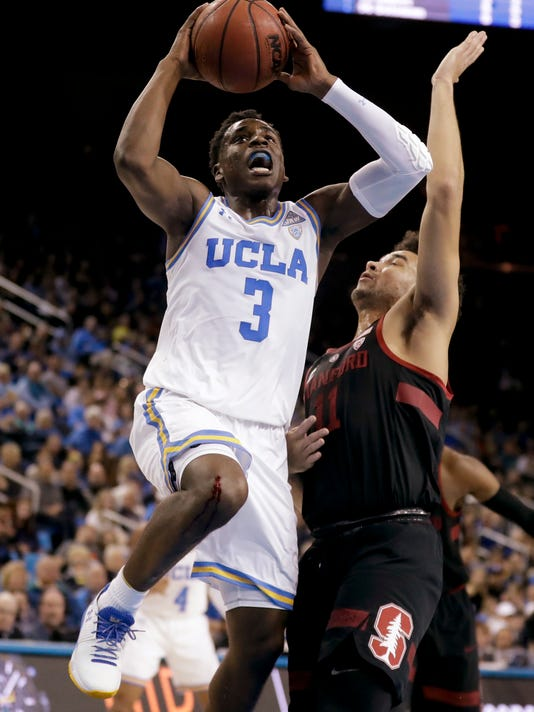UCLA guard Aaron Holiday, left, shoots next to Stanford guard Dorian Pickens during the first half of an NCAA college basketball game in Los Angeles, Saturday, Jan. 27, 2018. (AP Photo/Chris Carlson)