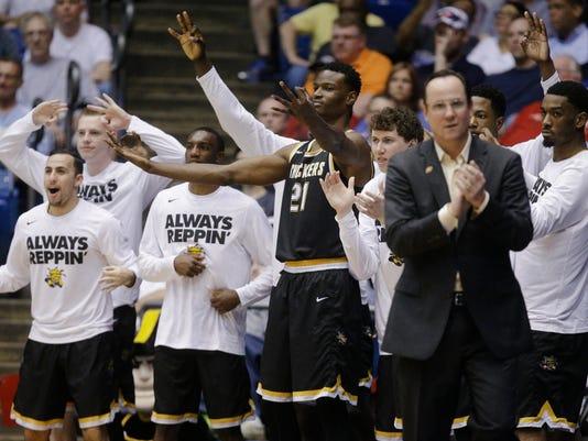 Wichita State's Bush Wamukota (21) and the Wichita State bench react during the second half of a First Four game of the NCAA men's college basketball tournament against Vanderbilt, Tuesday, March 15, 2016, in Dayton, Ohio. Wichita State won 70-50. (AP Photo/John Minchillo)