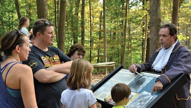 Visitors explore Deserted Village panels.