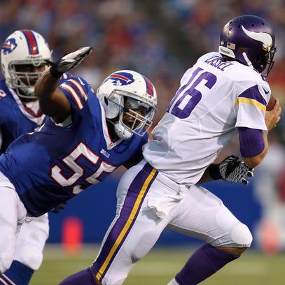 Bills linebacker Jerry Huges (55) pressures Vikings quarterback Matt Cassel.