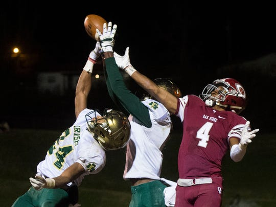 Oak Ridge's Caleb Martin (4) tips the ball out of Catholic's  Cameron Blakely (8) and DJ Mitchell's (24) hands during a TSSAA football play-off game between Knoxville Catholic and Oak Ridge at Oak Ridge Friday, Nov. 17, 2017. Catholic defeated Oak Ridge 28-37.