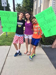 Vittoria Valentin and her sons pose with a poster advertising