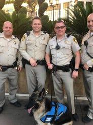 Shasha poses with Clark County Sheriff's deputies.