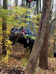 A vehicle wedged between two trees is removed.