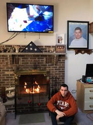Tyler Lewis poses under a portrait of his brother,