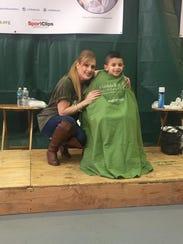 Volunteer barber Becki Stapleton sits with a shavee