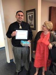 Jason Zigrand accepts a gift of recognition on behalf