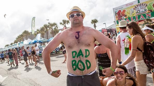 """A photo of man with """"Dad Bod"""" written on stomach."""